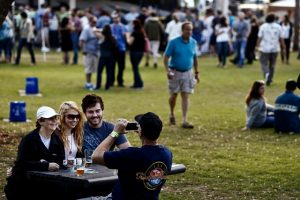 Tom Evans snaps a photo of Pam Evans, from left, Cori Evans, and Ryan Hoevenaar at Bonita Brew Fest at Riverside Park in Bonita Springs on Saturday, February 7, 2015. (Scott McIntyre/Staff)